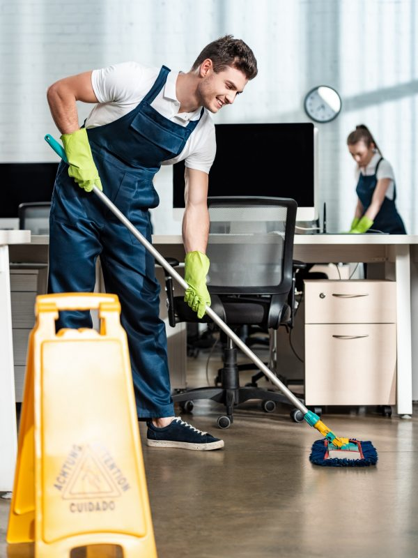 smiling cleaner washing floor with mop near colleague cleaning desk